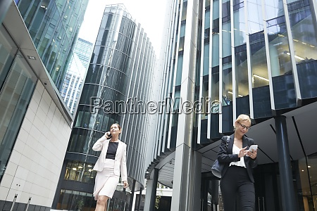 female professionals walking with mobile phones