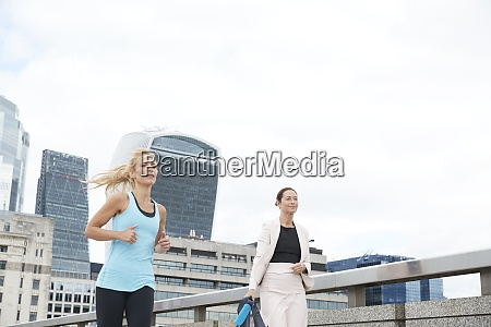 woman jogging by businesswoman carrying bag