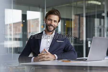 smiling businessman with hands clasped sitting