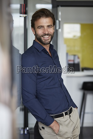 man with hands in pockets smiling