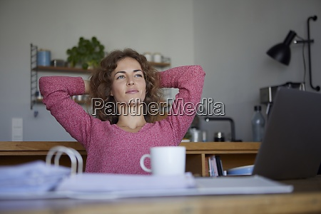 woman with hands behind head relaxing