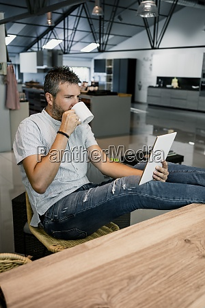 relaxed businessman looking at digital tablet