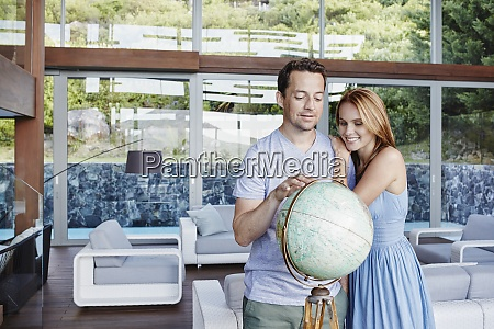 couple looking at globe while standing