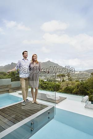 heterosexual couple looking away while standing