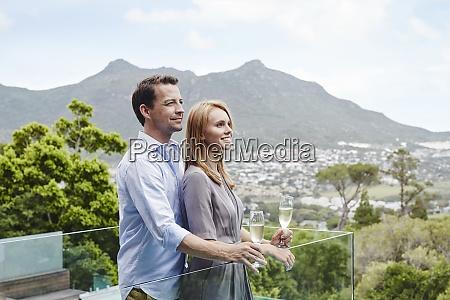 heterosexual couple holding wine glass looking