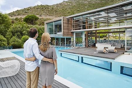 heterosexual couple looking at modern house