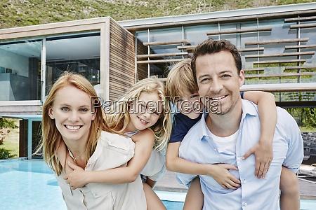 smiling family standing against modern house