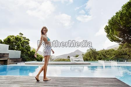 young woman wearing bikini standing near
