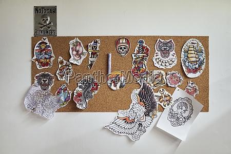 tattoo designs hanging on bulletin board