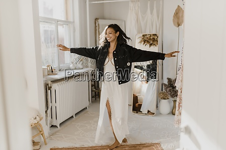 bride dancing with arms outstretched wearing