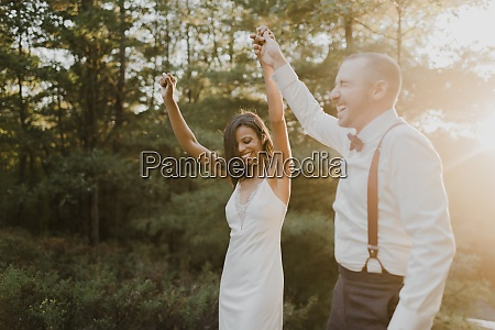 happy couple dancing in forest during