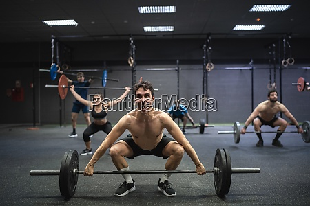 athletes picking barbell while exercising at