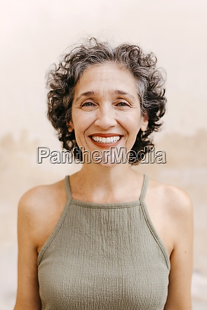 mature woman smiling while standing against