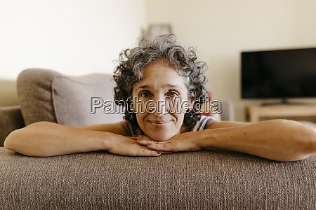 mature woman resting on sofa at