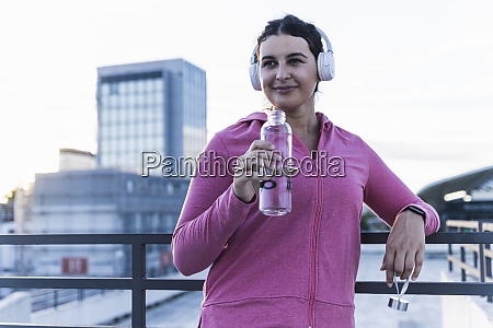 young woman holding water bottle listening