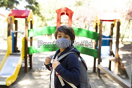 boy wearing mask with backpack standing