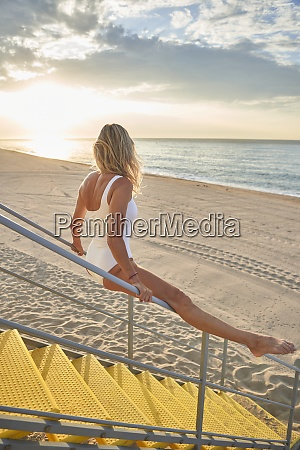 blond woman exercising on staircase railing