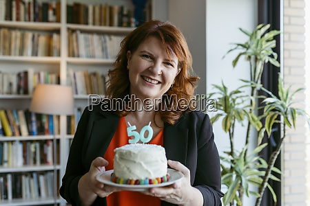woman holding cake with number 50