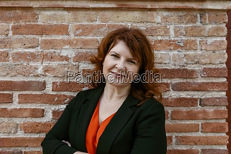 smiling woman standing against brick wall