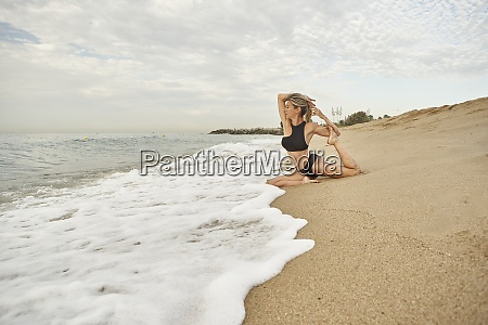 woman stretching legs and arms while