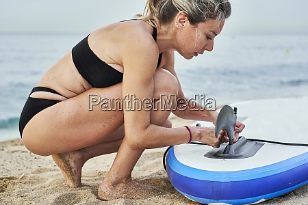 woman tying rope on surfboard while