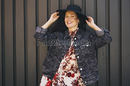 smiling woman with hat standing against