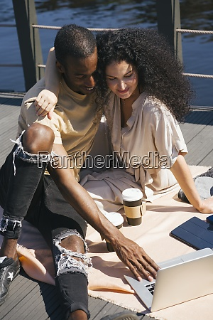 couple using laptop while sitting on