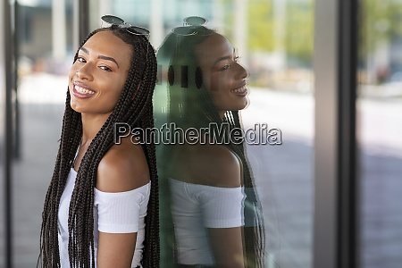 young woman smiling while leaning on