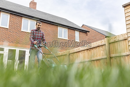man mowing lawn with lawn mower