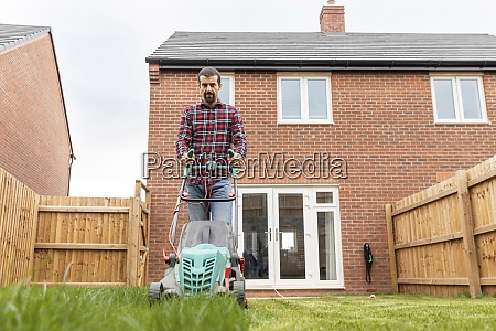 mid adult man using lawn mower