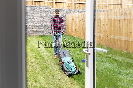 man mowing lawn with push lawn