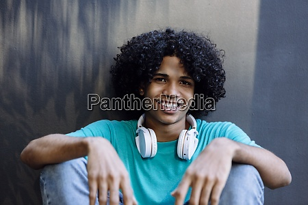 smiling hipster man sitting against wall