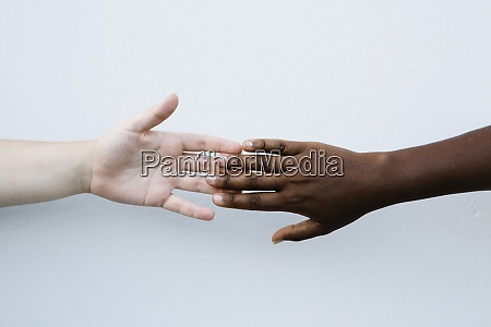 friends holding hand against white wall