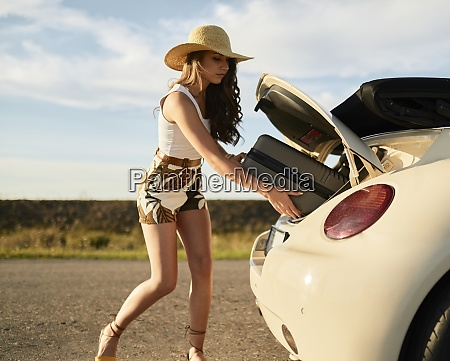 beautiful young woman removing suitcase from