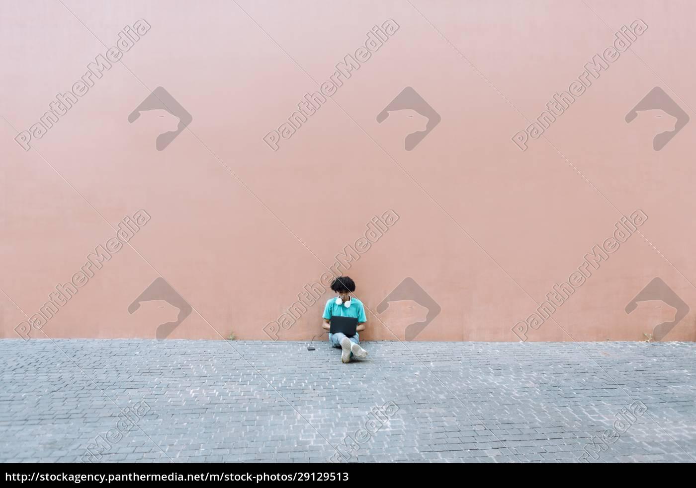 man, using, laptop, while, sitting, on - 29129513