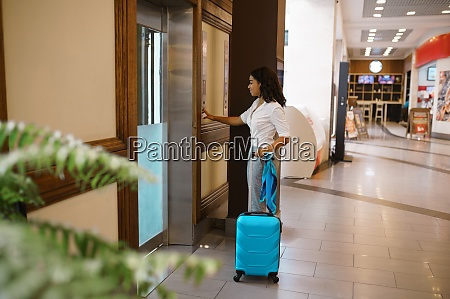 woman with suitcase calls the elevator