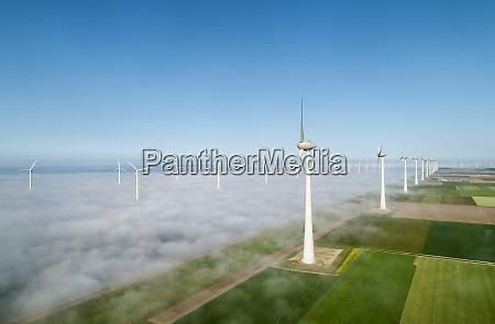 offshore wind turbines standing in fog