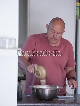 senior man mixing ingredients for cake