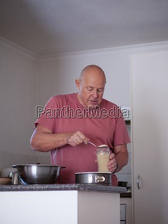 senior man preparing ingredients for cake