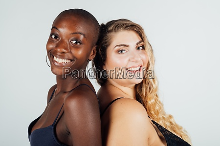 two young women smiling back to