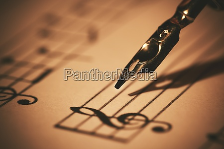 writing musical notes on sheet with