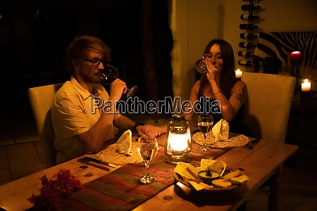 couple drink wine at table by