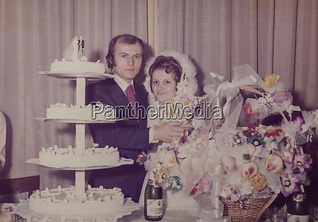 newlyweds with wedding cake 60s