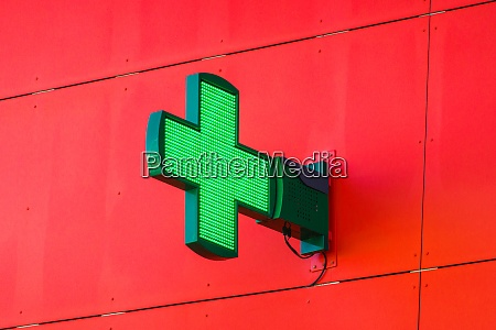 green pharmacy sign on red wall