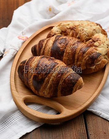 baked croissants lie on a wooden