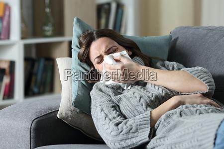 ill woman suffering flu symptoms blowing