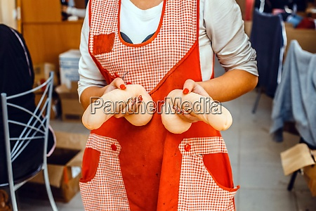 a worker holds rubber penises in