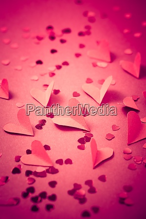 red paper hearts on red background