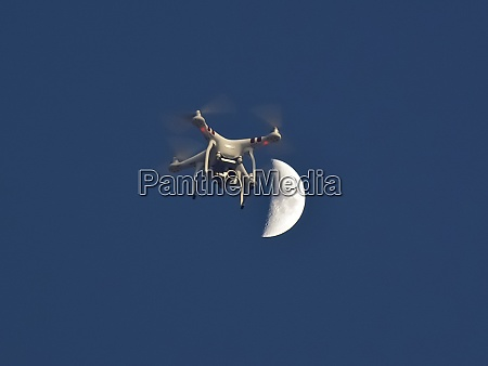 drone against moon and blue sky