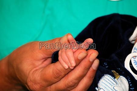 hand of a newborn touching finger